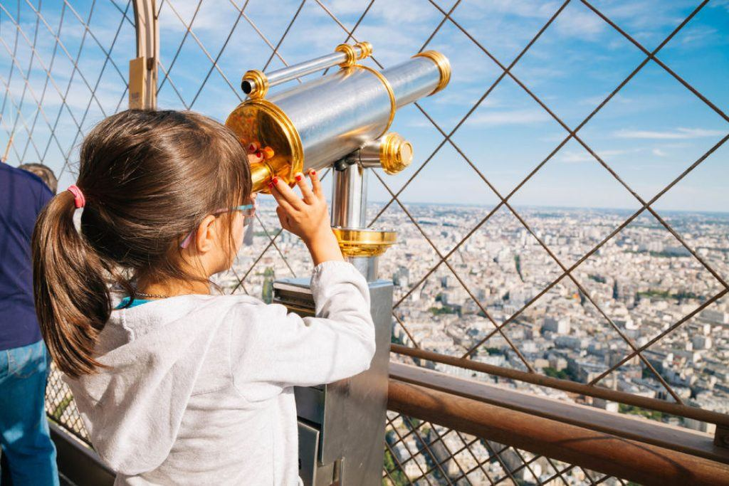 Girl looking through a telescope on top of the eiffel tower