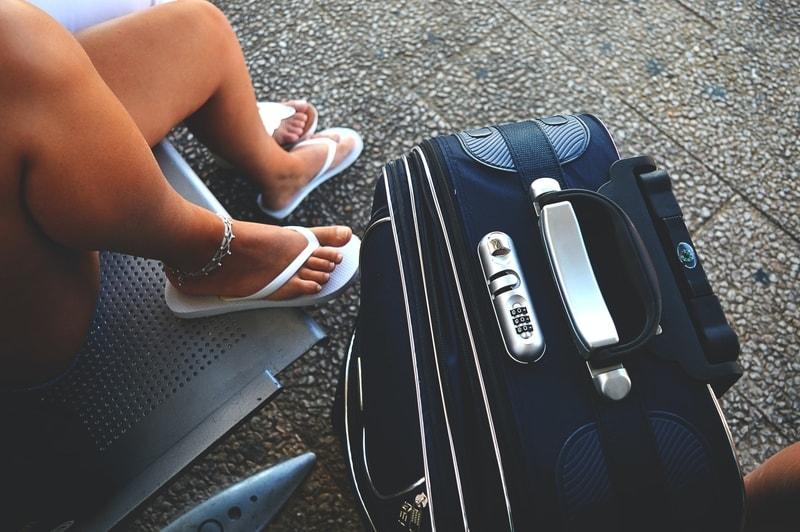 girl wearing flip flops sitting next to her travel suitcase